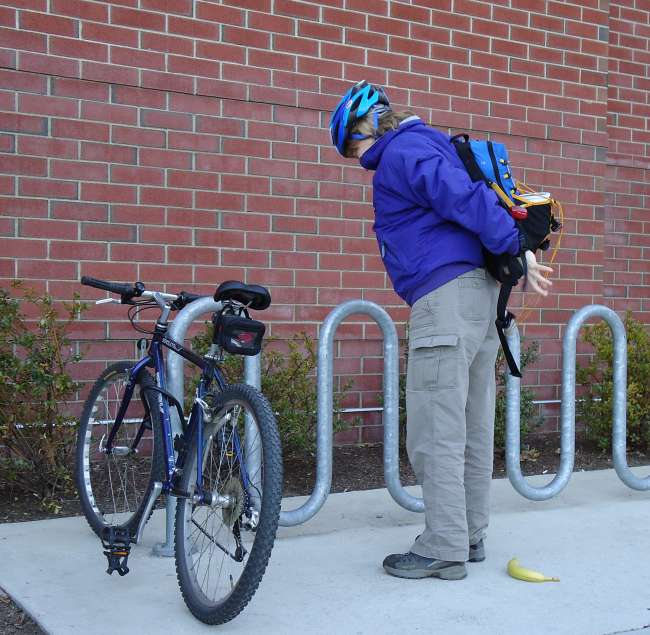 Cyclist Putting On Backpack