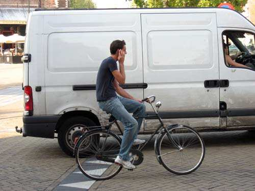 Man Riding Bike Using Cell Phone