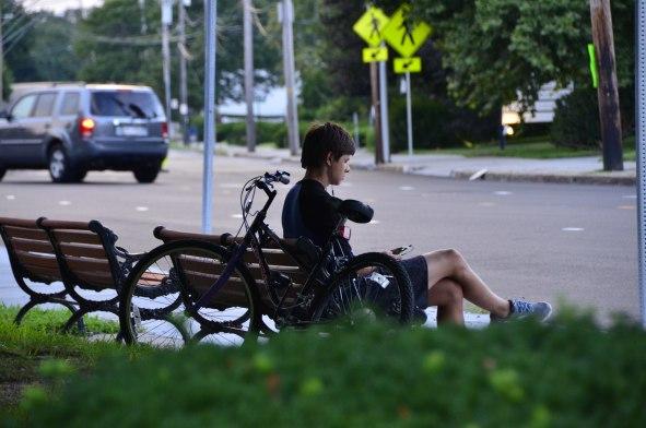 Cyclist Sitting On A Bench